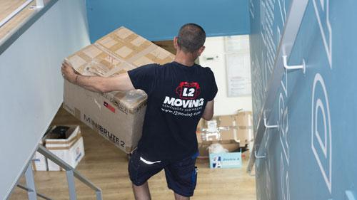 Demenageur transportant des cartons dans un local d'entreprise